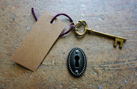 old fashioned: Key hole and old fashioned key with paper tag