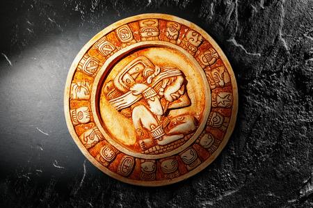 cultura maya: Calendario maya tallado en piedra sobre fondo oscuro