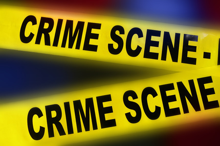 scene of a crime: yellow police crime scene tape on red and blue background Stock Photo