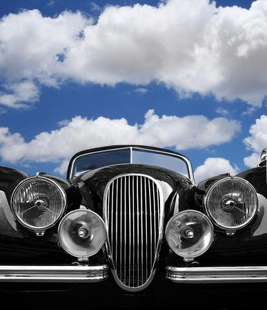 vintage car: Vintage car front view with blue sky clouds