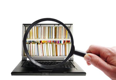 Hand met vergrootglas op zoek naar laptop met boeken Stockfoto