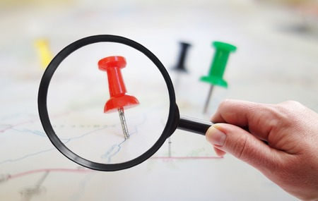 Magnifying glass looking at closeup of push pin tacks in a map Stock Photo