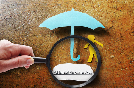 health care decisions: Paper person and Affordable Care Act umbrella under magnifying glass Stock Photo