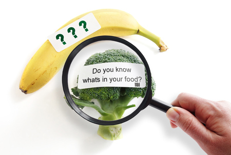 label sticker: Whats In Your Food label on broccoli with magnifying glass -- food safety or GMO concept Stock Photo