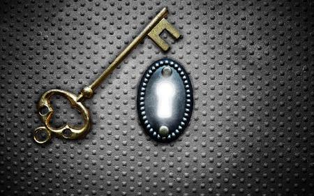 key hole: antique gold key and bright key hole on metal background Stock Photo