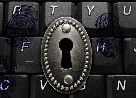 lock with keyhole on computer keyboard with fingerprints -- data security concept Stock Photo