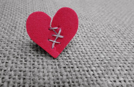 Broken red heart with white thread stitches