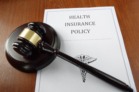 Health Insurance Policy document with court gavel Imagens