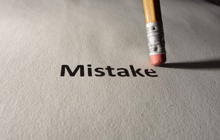 erased: Mistake text on paper being erased by a pencil Stock Photo