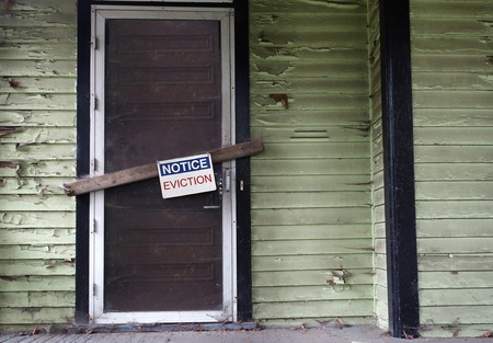 An old vacant house with Eviction Notice on door