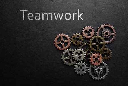 thinking machines: Assorted metal gears with Teamwork text on dark background