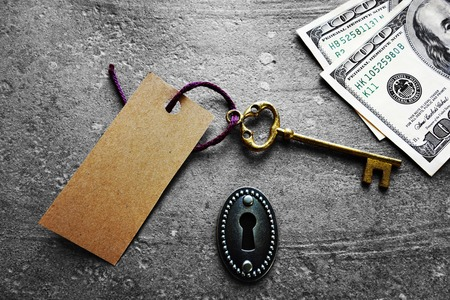 nestegg: Gold key with blank tag, with keyhole and cash Stock Photo