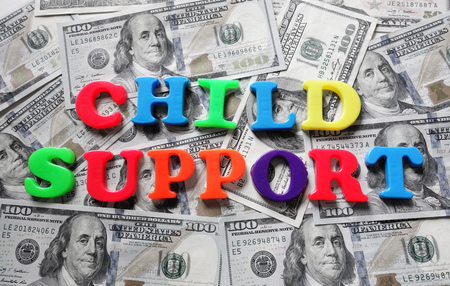 Child Support spelled in colorful letters on cash Stock Photo
