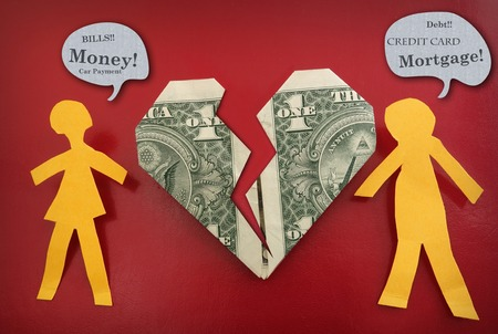 Paper couple fighting about money, with broken dollar heart Stock Photo