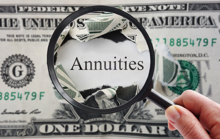 smart investing: Hand holding a magnifying glass over torn dollar bill with Annuities text