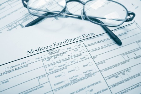 premiums: Medicare enrollment form and glasses Stock Photo