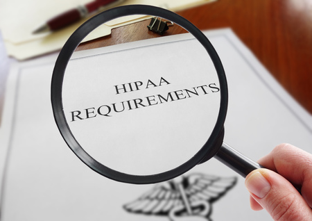 HIPAA healthcare requirements document with hand holding a magnifying glass