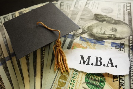 business degree: Mini graduation cap on cash with MBA paper note -- Masters of Business Administration degree concept