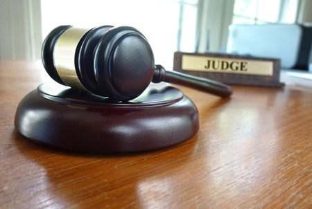 arbitrator: Court gavel on a desk with Judge nameplate in background