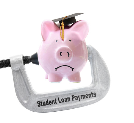 education loan: Frowning piggy bank wearing graduation cap being squeezed in a Student Loan Payments vice, on white - Stock Photo