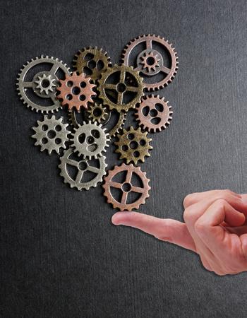 finger tip: Metal gears balanced on a finger tip Stock Photo