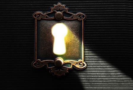 Licht scheint durch ein Schlüsselloch eines altmodischen Schloss