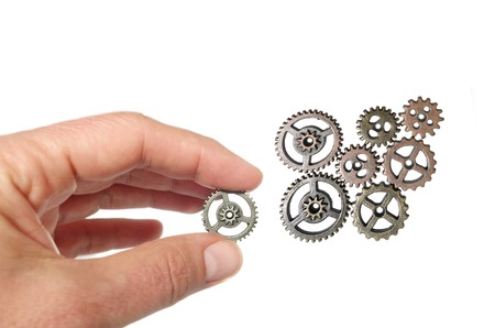 Hand placing a gear together with others, isolated on white Stock Photo