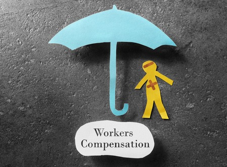 Injured paper man under an umbrella with Workers Compensation message Stockfoto