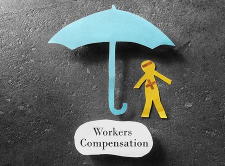 Injured paper man under an umbrella with Workers Compensation message Standard-Bild