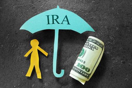 nestegg: Paper person under an IRA umbrella with cash Stock Photo