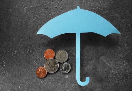 Coins under a paper umbrella -- financial security or retirement savings concept Foto de archivo