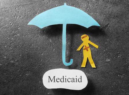 medicaid: bandaged paper man under umbrella with Medicaid message
