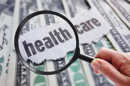health care decisions: Magnifying glass looking at health care newspaper headline, on cash