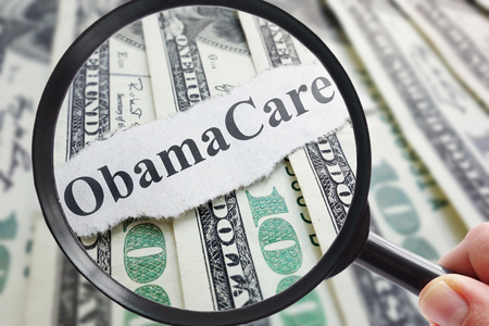 healthy economy: Obamacare newspaper headline on cash with magnifying glass