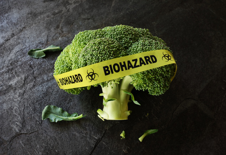 genetically modified crops: Yellow Biohazard tape on a piece of broccoli -- food safety concept