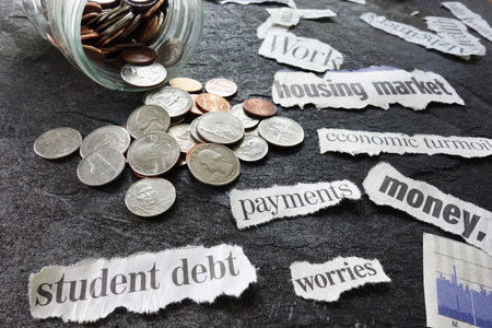delinquency: Assorted economy related newspaper headlines with coin jar Stock Photo