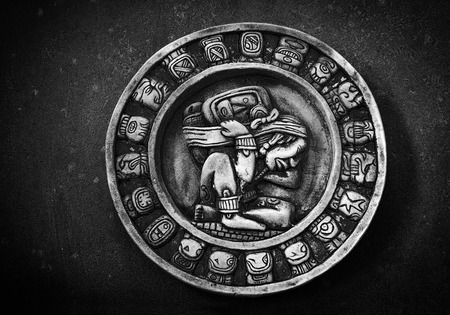 symbols: Carved circular Mayan calendar on textured background Stock Photo