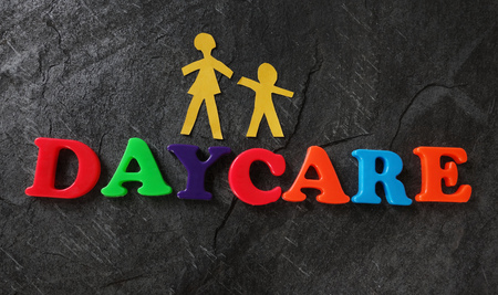 Daycare spelled out in play letters with paper mother and child