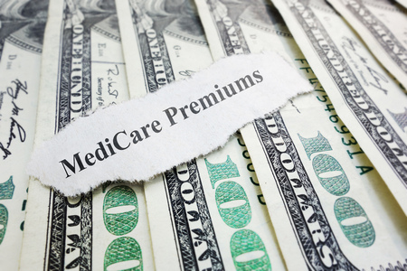 premiums: Closeup of Medicare Premiums newspaper headline on cash