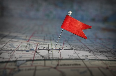 Pin with red flag stuck in a map Stock Photo