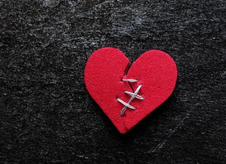 Red broken heart with thread stitches on dark background Stock Photo