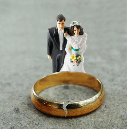 unfaithful: Bride and Groom figures behind a cracked gold wedding ring -- divorce or infidelity concept