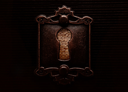 Keyhole on old fashioned door lock blocked by a brick wall