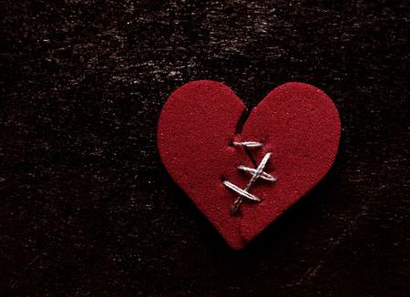 Broken red heart with thread stitches on grunge background
