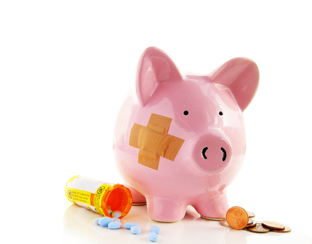 Bandaged piggy bank with pills and money Stock Photo