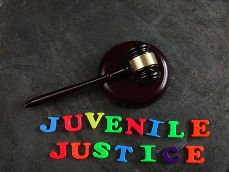 Juvenile Justice spelled out in play letters, with gavel 免版税图像