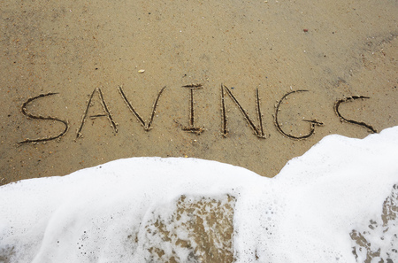 nestegg: Savings text written in the sand, being washed away by a wave -- Financial insecurity concept Stock Photo