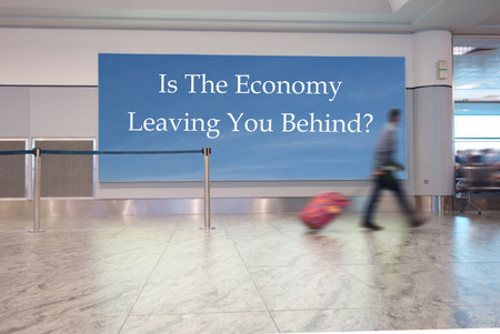 expertise: A man with suitcase walks in an airport, with Is The Economy Leaving You Behind? text on a sign Stock Photo