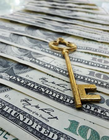 Gold key on assorted hundred dollar bills Stock Photo