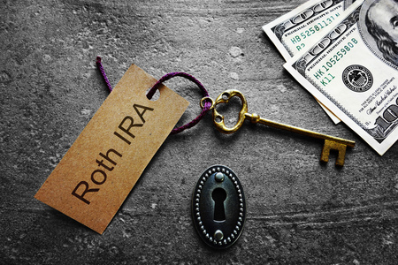 Gold key with Roth IRA tag, with keyhole and cash Stock Photo